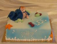 Namngivningstårta/doptårta med modellerad söt baby. Tårta klädd med sockerpasta, badbubblor av kristyr.
