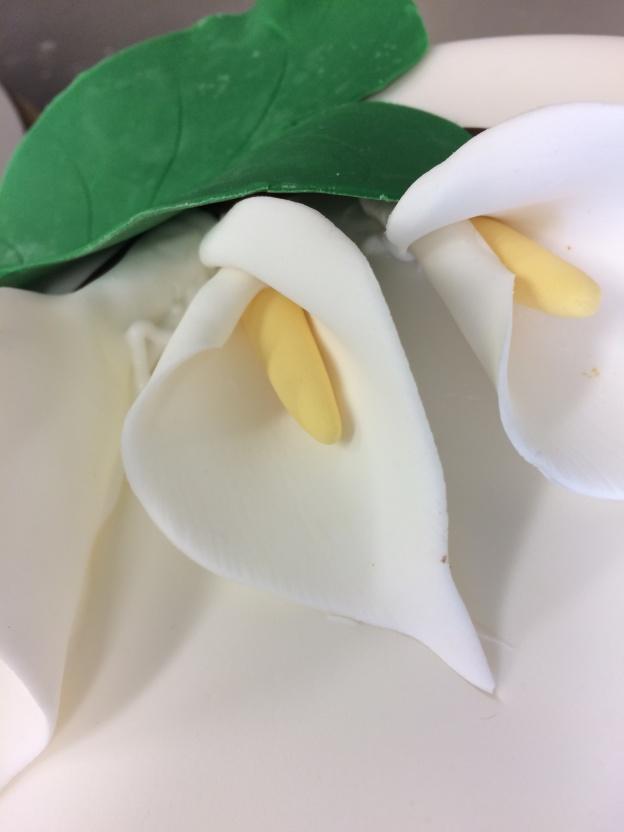Vita callaliljor med tillhörande blad.