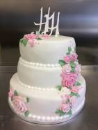 Fylld med passions- och päronmousse dekorerades denna trevåningstårta med rosor i rosa och ett monogram av flowerpaste.