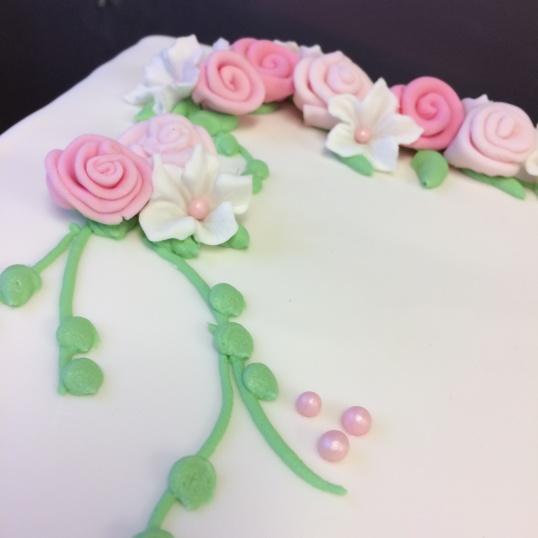 Söta sockerrosor, spritsade blad och petunior av socker samsades på tårtan