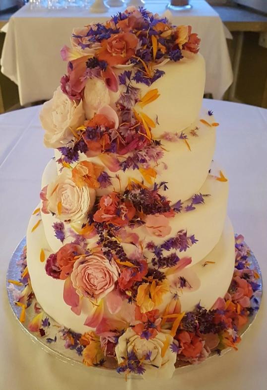 Våningstårta för bröllop dekorerad med ätbara blommor.