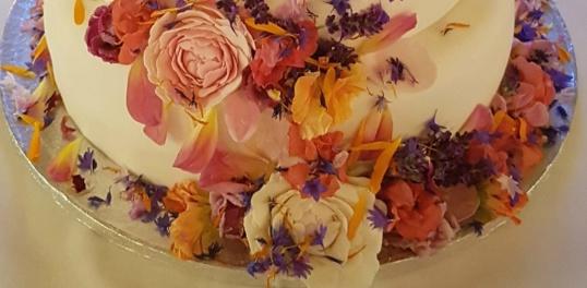 Tårtfatet dekorerades med ätbara blommor tillsammans med bröllopstårtan