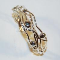 Armring i silver och guld samt blå diamanter