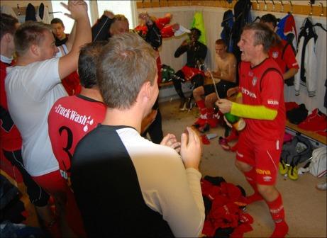Granlos Jesper Hellström, sprutar glatt ner sina lagkamrater med skumpa sedan föreningen för första gången tagit steget upp i Medelpadsfyran. Foto: Janne Pehrsson, Lokalfotbollen.nu.