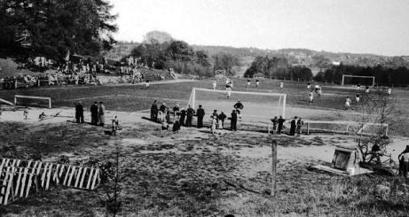 Försommaren 1936 var det fotbollsmatch mellan Sköns IF och Ljunga IF. I förgrunden handgrävd vattenbrunn där vattenhinken vevades upp med kättingspel. I pausen samlades spelarna runt brunnen för att släcka törsten i den mugg som syns hängande på veven. Målvakten drack sitt vatten från utsidan på sin kupade 30-talskeps och slapp därigenom att stå i kön bland de övriga spelarna. På kullen ovanför syns ställningar från stånd som användes vid de årliga sommarfestligheterna. 1939 byggdes omklädningsrum för spelarna. Även friidrott idkades på Flodbergsudden och förgrunden syns hoppgrop med höjdhoppsställningar. Ur Sköns Norra Intresseförenings samlingar 00053)
