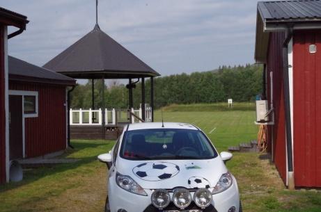 Lokalfotbollens vita Fårrd parkerad franför omklädningsbyggnaden och paviljongen med gräsplanen i bakgrunden. Foto: Pia Skogman, Lokalfotbollen.nu.