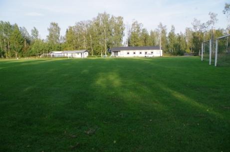 """Läktare, omklädning och klubblokal med planen i förgrunden. Det lilla vita längst till höger är Lokalfotbollens """"Fårrd"""" vid entrén. Foto: Pia Skogman, Lokalfotbollen.nu."""