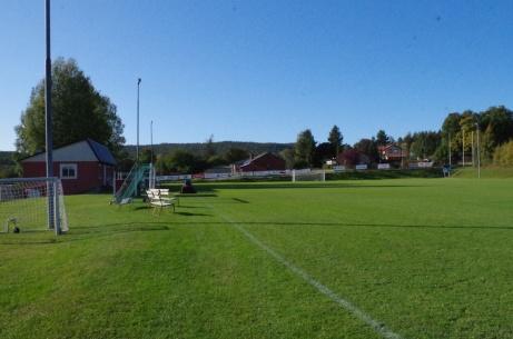 Blick över planens längdriktning mot avbytarbåsen och klubbhuset. Foto: Pia Skogman, Lokalfotbollen.nu.