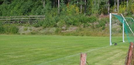 Huvudläktaren halvvägs upp i skogen sedd från parkeringen. Foto: Pia Skogman, Lokalfotbollen.nu.