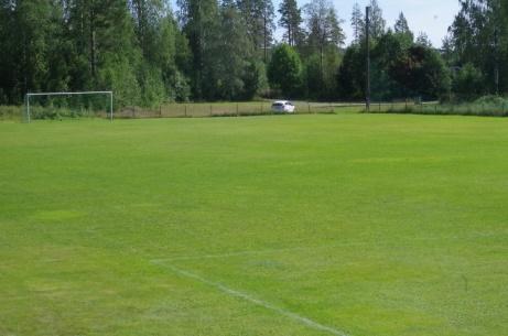 Vy över Hasselbackens gröna gräsrektangel med parkeringen i bakgrunden. Foto: Pia Skogman, Lokalfotbollen.nu.