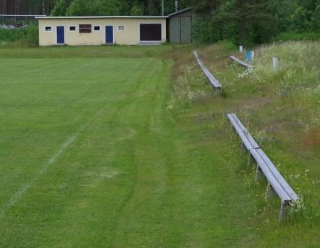 Läktarna till höger och förrådsbyggnad längre bort, med matchuret. Foto: Pia Skogman, Lokalfotbollen.nu.
