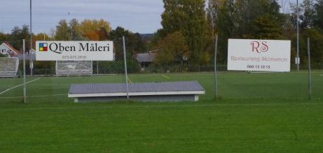 Ett par sponsorskyltar och konstgräsplanen nedanför. Foto: Pia Skogman, Lokalfotbollen.nu.