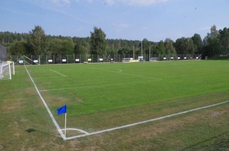 Utsikt över en grön höstplan med avbytarbåsen i bakgrunden. Foto: Pia Skogman, Lokalfotbollen.nu.