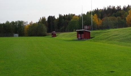 Avbytarbåsen och speakerbåset mellan flaggstängerna. Foto: Pia Skogman, Lokalfotbollen.nu.