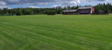 Nyklippt gräsmatta med den mäktiga föreningsbyggnaden med omklädning, servering, klubblokal med mera. Foto: Pia Skogman, Lokalfotbollen.nu.