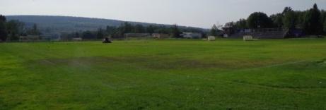 Vy över planen från entrén, gräsklippning pågår. Foto: Pia Skogman, Lokalfotbollen.nu.