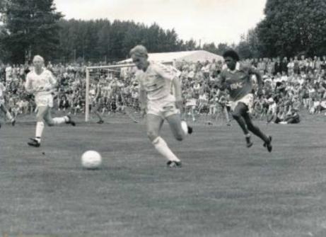 """Det portugisiska storlaget Benfica med bland annat Jonas Thern besökte Slädavikens IP i juli 1991 för en sommarmatch mot Alnö IF. Cirka 4 500 åskådare, inkl. den blivande """"lokalfotbollaren"""" hade tagit sig till den vackra idrottsplatsen för att bevittna matchen. Förutom grässluttningarna så hade särskilt uppbyggda läktare tagits i anspråk. På bilden är det Robert Lindmark som försöker hålla undan för en av portugiserna. I bakgrunden finns Stefan Andremo och i målet syns Ulf Jonsson. Foto: Alnö IF."""