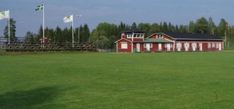 Blå himmel, flaggor. läktare och klubbyggnaden sedd från andra sidan planen. Foto: Pia Skogman, Lokalfotbollen.nu.