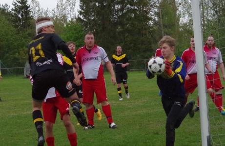 Joel Eriksson (nr 21) sätter huvudet till på en hörna men Andreas Kallberg i Stockviksmålet greppar säkert bollen. Foto: Pia Skogman, Lokalfotbollen.nu.