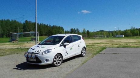 """Lokalfotbollens vita """"Fårrd"""" snyggt parkerad framför Torpshammars IP:s gräsrektangel. Foto: Pia Skogman, Lokalfotbollen.nu."""