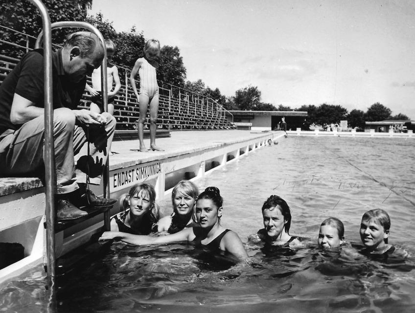 Birger Buhre på bassängkanten i Malen/Båstad med i vattnet frv. Marianne Stridh, Evy Sätherström, Marianne Sjöström, Ingrid Ahlström, Marie Nilsson och Lisbeth Sandgren.