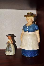 Min 25 cm höga torggumma, ihop med mormors 13 cm höga keramikflicka.  I kjolen till den lilla hänger i en ståltråd en keramisk klockkläpp. Den är alltså även en klocka.