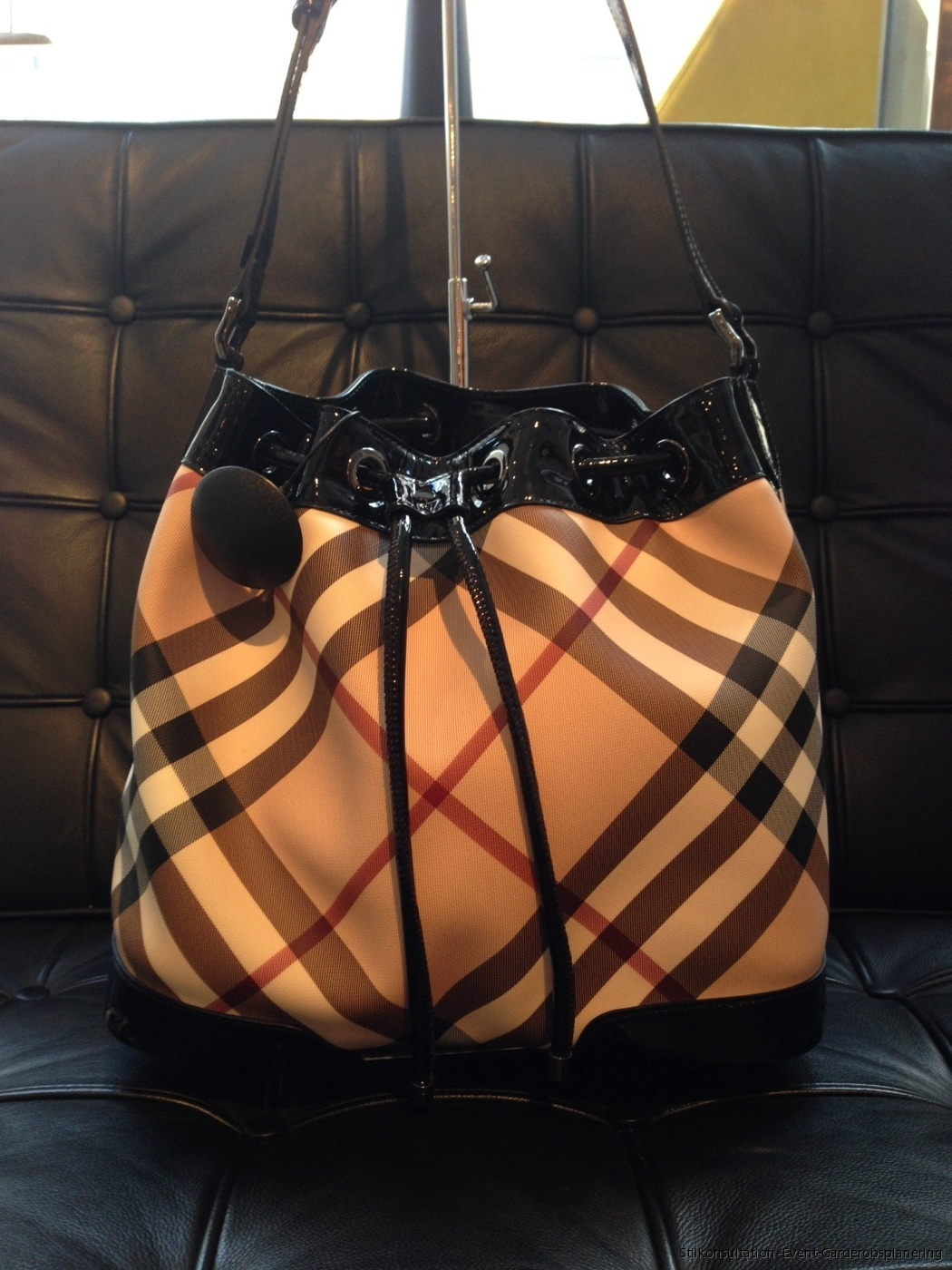 6acff0c66ac3 Gorgeous drawstring bucket bag with a long strap from Burberry is the perfect  go-to bag when you re out and about. The classic combo of black patent  leather ...