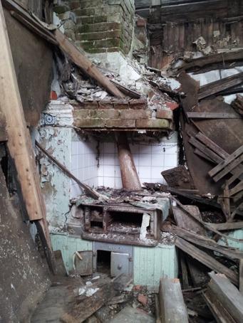 Järnspisen står kvar, murstocken är förvånansvärt intakt. Innerväggarna har bestått av smala spontade brädor. Inredningen är 50-tal gissar jag på. Några väggskåp finns kvar och en vedlår är inbyggd bredvid spisen. Takbjälkarna som gått av ligger framför spisen.