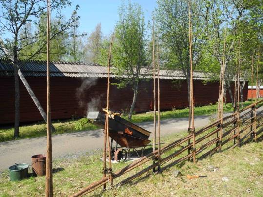"""En bild från när vi byggde gärdsgårdar på Gammlia ifjol! I bakgrunden vår """"drake"""" där vi värmer vidjorna som vi binder ihop allt med."""