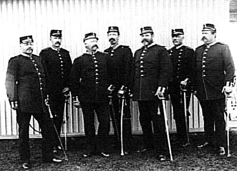 Bild från Västergötlands Museum - bildarkivet/bildnummer: B145048. Fanjunkare nr 7 från vänster är sonen till fanjunkare Carl Samuel Philip Flach - Carl Gustaf Flach, född 1841 - alltså längst till hö