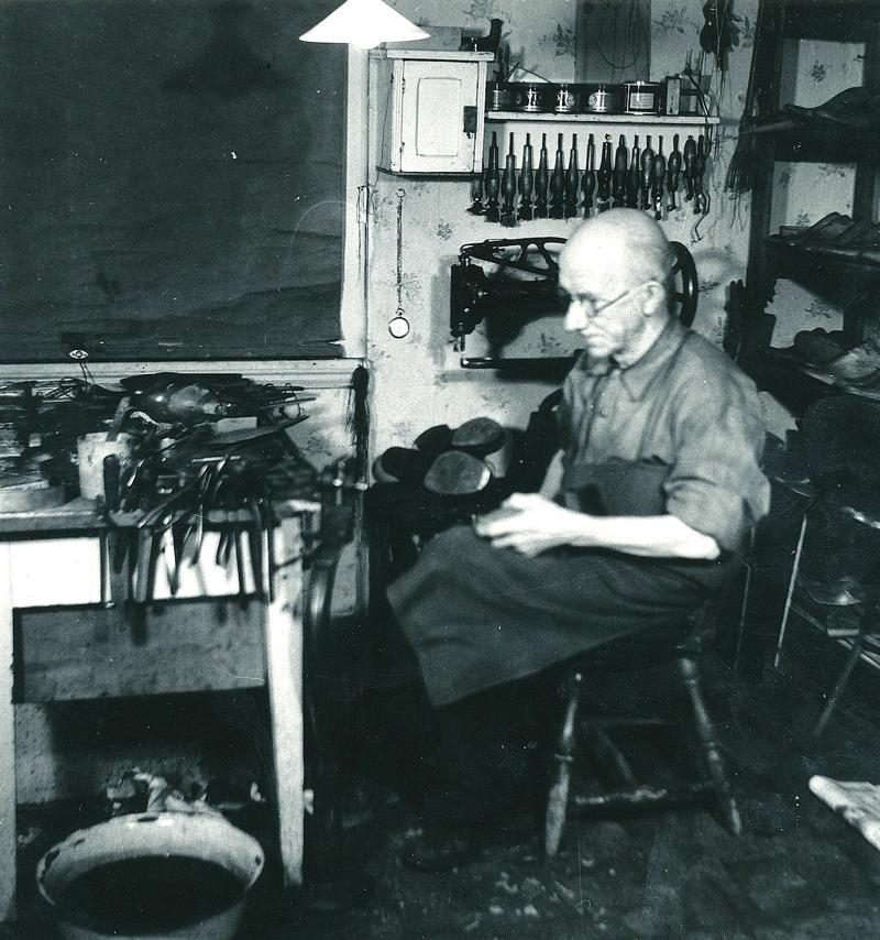 C. 1 Skomakare Gustav Larsson i sin verkstad i början av 1950-talet. Han bodde tidigare i Kullen (vid Kyrkebo Allé) men byggde på 1930-talet villan Munkedal där han även hade sin verkstad. Larson var känd och ansedd som en skicklig utövare av sitt yrke. Han upphörde med verksamheten 1955 och flyttade med familjen till Jönköpiing. Insatt av Kent Friman, 2014-02-26.