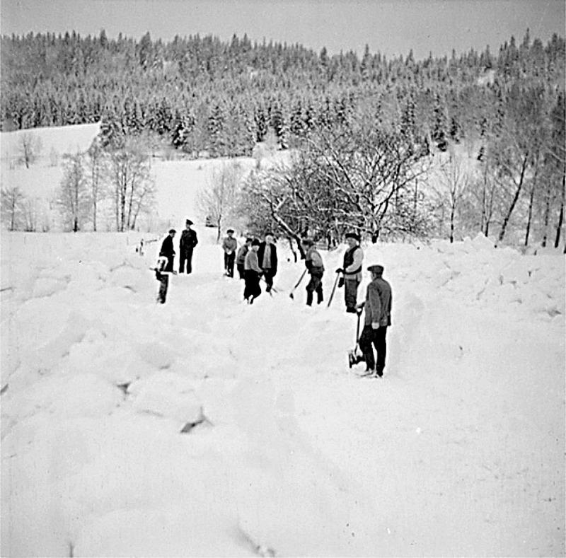 C. 17 - obs! av KF vänd bild - måste ha blivit felvänd på papperkopian!  I början på 1940-talet var svåra snövintrar och vägarna blev ofta ofarbara med upp till 2 m djupa drivor. Här ett uppbåd som gräver upp Fermagatan (vägen upp till Ljungstorp). Bland männen kan igenkännas fr.v. Teodor Krantz, Erik Lann, David Johansson och Oskar Larsson.  Längst ner väntar Samuel Friman, med taxiuniform och taxiskärmmössa, på att få komma fram med sin taxi.  Fotograf: Nils Lann, Ljungstorp/Varnhem samt uppgifter.  Fermagatan strax nedanför Vibonätt och Vadet ner mot landsvägen. Här kan man ännu se de fruktträd till höger som hört till trädgården för Stensbro - det hus som fanns här utmed Fermagatan nära bäcken utmed landsvägen nere i dalen. Insatt av Kent Friman, 2014-02-26. läs mer på www.ljungstorpshistoria.se!