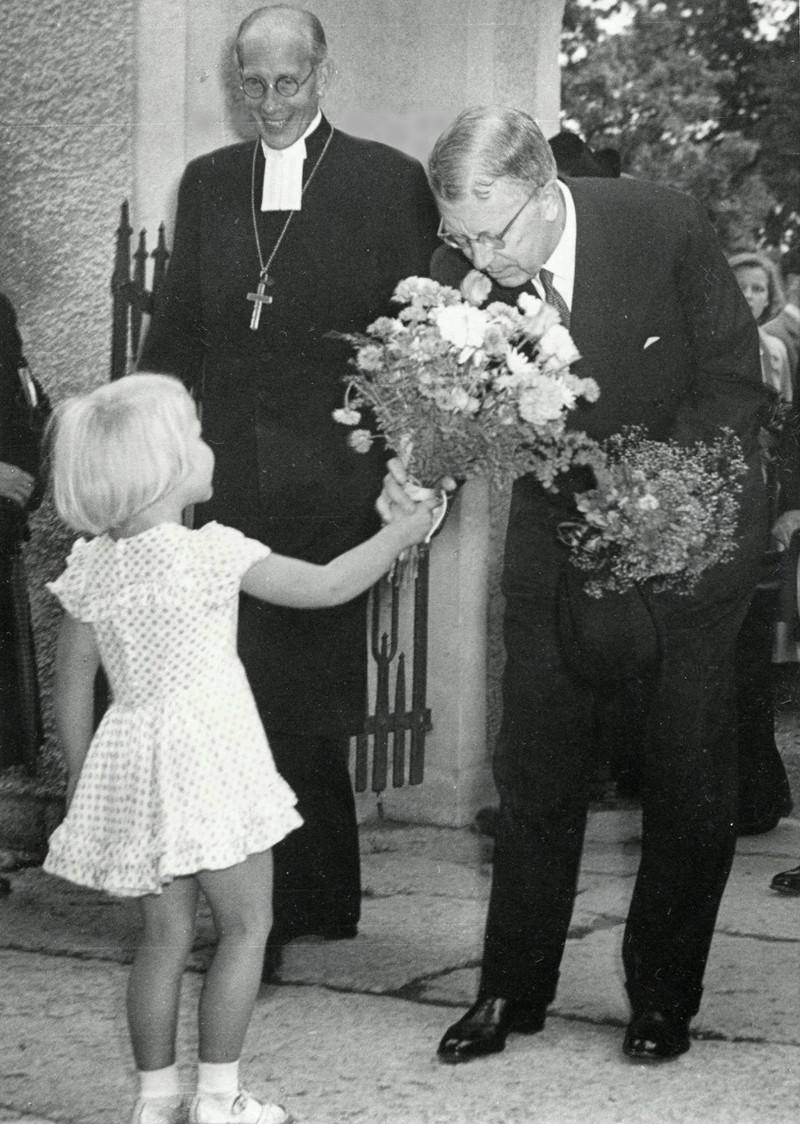 D. 17 (4) Lilla fröken Hermansson överlämnar blommor till kung Gustaf VI Adolf i entréporten till kyrkan. Biskop Rudberg ler stort. Insatt av Kent Friman, 2014-02-27. Klicka på bilden för att se den mindre!
