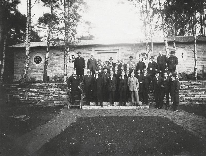 """D. 2 (2) Jämför gruppfotot med namnat gruppfoto nr; D. 13. Invigning av Varnhems Klostermuseum 1928. """"Den vidgade kretsen"""". Mannen längst till höger på muren är Johan Ohlsson, kyrkvaktmästare under flera årtionden. Lägg märke till två kvinnor längst bak i gruppen!  Insatt av Kent Friman, 2014-02-27."""