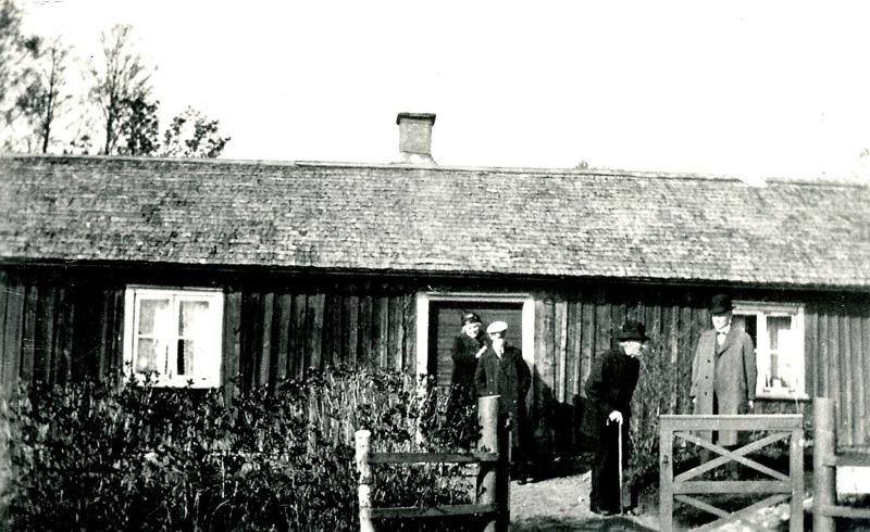 """A. 32 (1) Bäckedalen runt 1930. Gamla stugan i Bäckedalen, där Petter Lindqvist bodde och troligen undervisade skolbarn under 1830-40-talen. På bilden står från vänster Petters sonsons hustru, ett barnbarnsbarn, Per Hålltorp (med käpp) omkring 95 år gammal och Arvid på Hålltorp, son tilll Per. Naturnamnet Bäckedalen kommer sig naturligt av den djupa bäckravin som finns inom området som grundar upp fram emot Ljungstorspsvägen på Flinkebackens mark. Det lär ha funnits en skvaltkvarn nära platsen på Flinkebackens mark - en kvarn för husbehovs-malning. Det finns på karta 1882 en damm-markering på den intäkten.  Bäckens ravin har också naturligt skapat gränserna för de många små intäkter och boplatser som skapades här - främst under 1800-talet. Här bodde också David och Josefina Roth (""""Fina""""). Stugan revs 1938 och den nuvarande uppfördes till stor del av timmer från det rivna hemmanet Sten. Insatt av Kent Friman, 2014-02-24. Läs mer på www.ljungstorpshistoria.se!"""