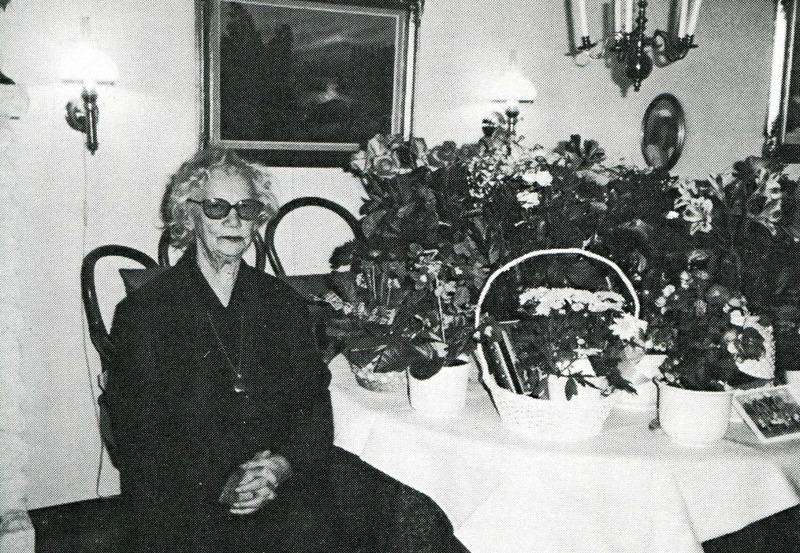 """G. 14 Endast digital bild!  Edith Pettersson på sin 85-årsdag 1997 i Vallehemmet. Bild från Varnhemsbygden 1998. De byggde snart till en del för utvidgning av caféet mot öster, bakom kiosken på bilden. Några av de unga Varnhemsborna på den tiden samlade på trappan till Caféet med goda smörgåsar och annat gott annonserat på fönsterrutorna. Cloetta mjölkchoklad och Marabou mjölkchoklad fick båda plats med reklamskyltar på taket till kiosken. I bakre raden skall enligt dottern Roland Johansson finnas.  Runhem var också plats för skolbespisning för Varnhemseleverna under 1960-talet med Edith Pettersson som matvärdinna.  Bakom Runhem till höger skymtar dåvarande Församlingshemmet, som också var småskola för 1:a och 2:a klass under ett antal år. Därefter kommer ladugården för Trädgården med gavel mot landsvägen, som också var en av de byggnader som försvann i o m Varnhemsbranden 1979. Den är återuppbyggd för annat ändamål.  Om någon vet vem som är vem på bilden - så hör gärna av er! <-- Till sidans topp!  Edith Pettersson på sin 85-årsdag 1997 i Vallehemmet. Bild från Varnhemsbygden 1998 Edith Pettersson på sin 85-årsdag 1997 i Vallehemmet. Bild från Varnhemsbygden 1998 När Erik och Edith Pettersson kom till Runhem från Kålland utvecklades både Café - och kioskverksamhet.  Där blev ett gott tillhåll för de som närmades sig tonåren, men också för dem som kommit upp i motoråldern. Edith kunde verkligen """"ta"""" ungdomarna på rätt sätt och de flesta kände sig som hemma. Hon anställde många ungdomar genom åren att arbeta både i Caféet och inte minst i kiosken.   Kiosken hade sin höjdpunkt inte minst när Västgöta-Bengtsson kom med sina militärresor med hundratals värnpliktiga och befäl för Klosterguidning. Då skulle det gå snabbt och glassarna fick plockas från botten av frysen innan alla hade fått köpa sin.  Puckstång 30 öre, God-ice 60 öre, Storstrut 1:25 och för 2:25 kunde man köpa en halvliter och den delades då i två delar och skedar lånades ut.   Det gällde också för de kios"""