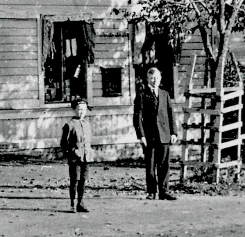 A. 6 (1) Endast digital bild - detalj. Nydal. Anton Larssons diversehandel. Några år efter övertagandet 1914 och Anton, född 1872 och hans äldste son Sixten, född 1908, poserar framför affären med stängd ytterport. Anton verkar som handlare till sin död den 25/11 1936. Hustrun Elsa Katarina Ingeborg Kronlund, född i Fridene 1882 den 10/4. Dottern Margit Elsa Kristina, född i Kyrkefalla 1906 den 5/4. Sonen Sixten Wilhelm Leopold, född i Kyrkefalla 1908 den 29/7 - dör strax innan sin far den 27/5 1936. Sonen Bertil Ivar Torsten, född i Kyrkefalla 1914 den 26/11. Lägg märke till de smidda reklamskyltarna som sitter fastskruvade på husväggarna. SAJ-järnvägen skymtar till vänster. Insatt av Kent Friman, 2014-02-14. Läs mer på www.saj-banan.se!