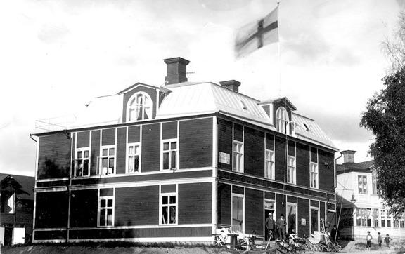 August Gustafsson nya pampiga affärsbyggnad  efter branden 1907. Troligen August och Ernst på trappan!