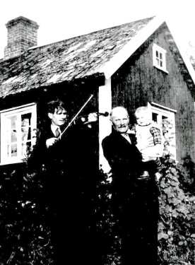 En spelman spelar fiol för Oscar Ekblad och hans dotterdoter Eivor, dotter till Elsa och Gustaf,  vid Jägarebacken 1933