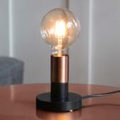 Svart lampa med kopparfärgad lamphållare