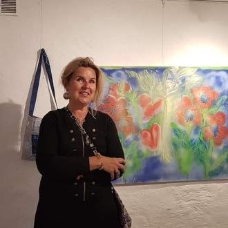 Christina framför en av hennes vackra tavlor.