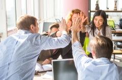 Bilden visar en arbetsgrupp som gör high five
