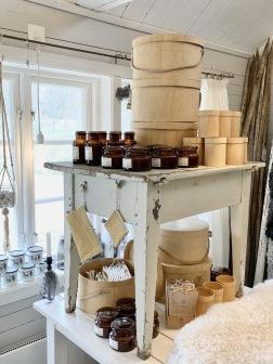 Igårdsbutiken finns det även plats för noga utvald inredning som tex  denna. Hattaskar i trä, doftljus och börser från Strömshaga och emaljmuggar från Maria Ringström.