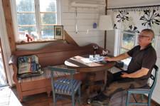 Bild på vardagsrum med gammal kökssoffa och man som  fikar.