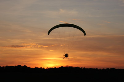 Tandemparamotor inför landning i solnedgången