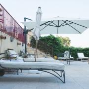 Terrassen med solstolar och parasoll.