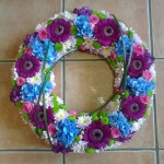 krans i mixade färger, nejlikor, gebera, hortensia, chrys, rosor m.m