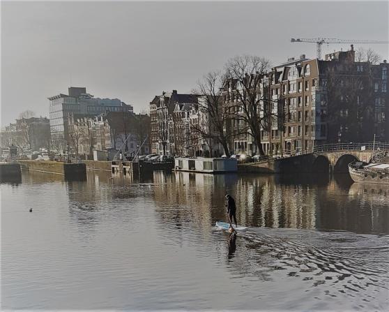Hälsosam normalviktig amsterdamare på planka i Amstel.
