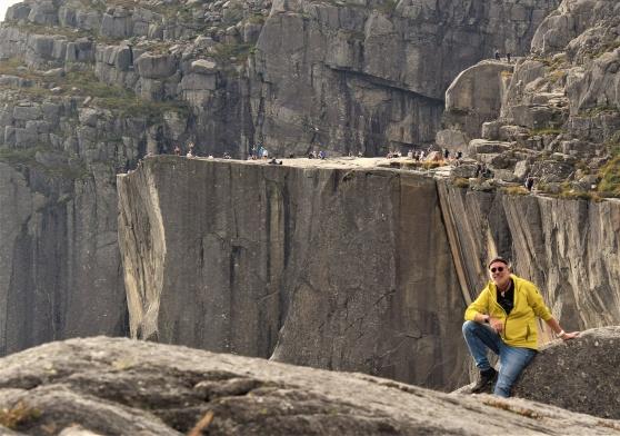 Nöjd turturist efter att ha bestigit Preikestolen i bakgrunden. 604 meter upp, eller fyra kilometer vandringsled.