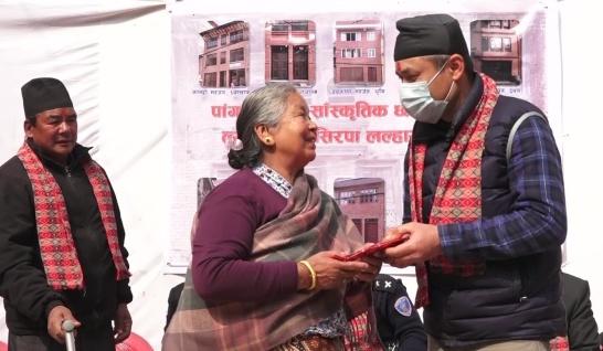 Vår projektledare Shekhar Dangol lämnar över pengar till en av familjerna i Nepal som fått hjälp med att bygga upp sitt hus efter jordbävningen. I bakgrunden syns en plansch med några av husen.
